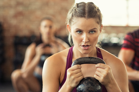 Portrait of concentrated young woman working out with kettlebell at crossfit gym. Closeup face of determined girl doing squat session while holding kettlebell and training biceps. Fitness class lifting heavy weights while squatting.