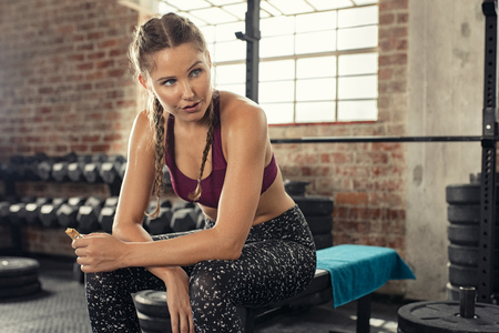 Sweaty young woman eating energy bar at gym after strong workout session. Beautiful exhausted woman enjoying chocolate bar after a heavy workout in fitness gym. Fit tired girl sitting and biting a snack while resting after training with copy space.