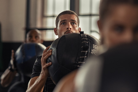 Portrait of young man lifting medicine ball with class in fitness center. Strong athlete doing crossfit training at gym. Guy holding heavy ball and doing squat exercise.