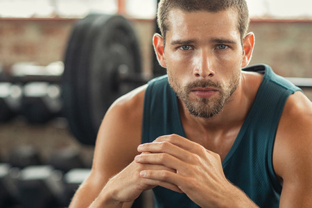 Handsome young muscular man resting in gym while looking at camera. Portrait of competitive and confident sportsman at crossfit center. Determined sweaty guy taking a break after working out session with copy space. Standard-Bild