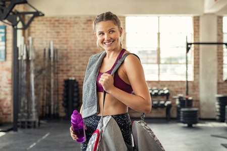 Young smiling woman in sportswear carrying gym bag. Happy fitness girl with water bottle and sports bag after exercise. Portrait of energetic beautiful woman looking away ready for new inscription at the gym.