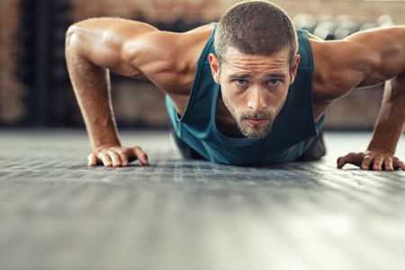 Junge Sportler, die Liegestütze im Rahmen des Bodybuilding-Trainings machen. Muskulöser Typ macht einen Liegestütz auf dem Boden im Crossfit-Fitnessstudio. Entschlossener athletischer Kerl im Sportbekleidungstraining.