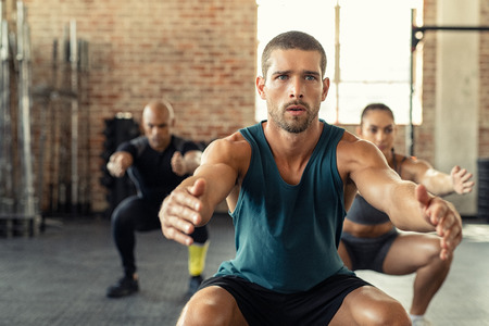 Young man exercising with squat in gym with people in background. Fit man exercising with stretched hands and squats at gym. Fitness class squatting togeher with outstretched during an exercise. Stok Fotoğraf