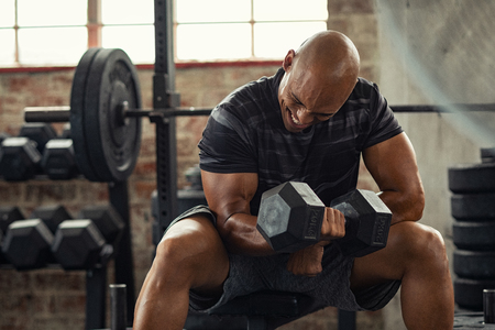 Muscular guy in sportswear lifting dumbbell while sitting on bench at crossfit gym. Mature african american athlete using dumbbell during a workout. Strong man under physical exertion pumping up bicep muscule with heavy weight.
