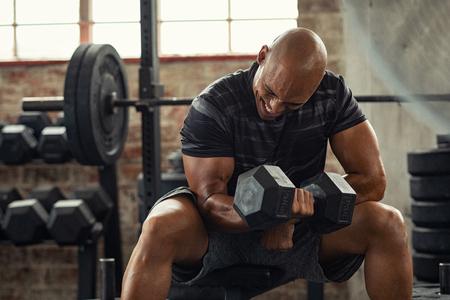 Muskulöser Typ in Sportbekleidung, der Hantel hebt, während er auf der Bank im Crossfit-Fitnessstudio sitzt. Reifer afroamerikanischer Athlet mit Hantel während eines Trainings. Starker Mann unter körperlicher Anstrengung, der den Bizepsmuskel mit schwerem Gewicht aufpumpt.
