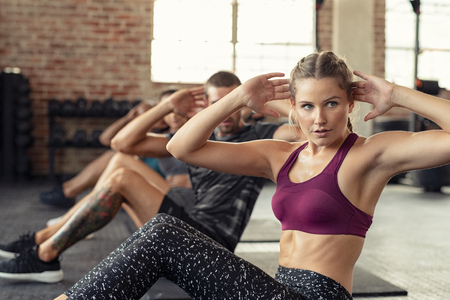 Young fitness woman doing abdominal exercise at gym. Concentrated people in a row doing sit ups on yoga mat. Training class doing situps at crossfit center.