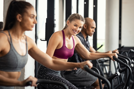 Fit woman working out with class on stationary bike at gym. Portrait of young beautiful woman smiling and looking at camera while cycling at gym. Happy cheerful athletes in a row training on exercise  写真素材