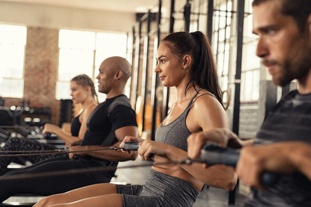 Group of people exercising in gym using rowing machine together. Side view of sportswoman doing exercise on rowing machine in crossfit center. Muscular girl and sporty men workout on training simulator at cross fit gym.