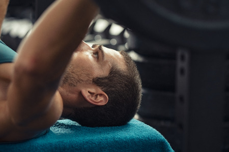 Young strong man doing weights on bench press. Closeup face of fitness guy on bench press lifting weight at cross fit club. Sports guy doing exercise at the crossfit gym. Stock Photo