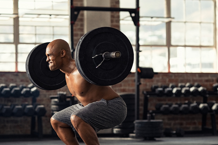 Determined african american man lifting weight in gym. Muscular strong man taking efforts to lift weight barbell in fitness center. Black shirtless bodybuilder doing squatting with a barbell on shoulder.