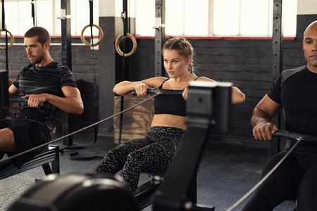 Giovane e bella donna che si allena con vogatore in palestra crossfit. Classe atletica facendo esercizio con vogatore. Gruppo di persone concentrate nel fitness nella formazione di abbigliamento sportivo.