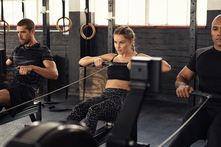 Young man and beautiful woman working out with rowing machine at crossfit gym. Athletic class doing exercise with rowing machine. Group of fitness concentrated people in sportswear training. Stock Photo