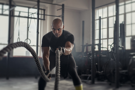 Athlete working out with battle rope at gym. Bald african man training using battle ropes. Fit sportsman doing crossfit exercise in an industrial dark gym.