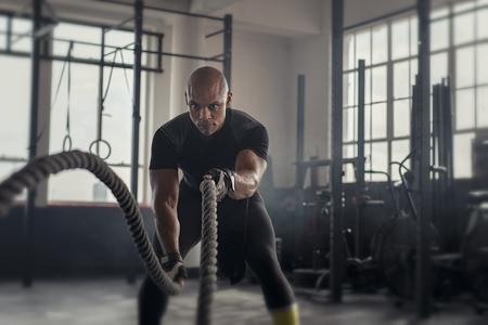 Atleta che si allena con la corda da battaglia in palestra. Uomo africano calvo che si allena usando corde da battaglia. Sportivo in forma che fa esercizio di crossfit in una palestra scura industriale. Archivio Fotografico