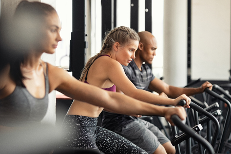 Group of determined multiethnic people at gym exercising on stationary bike. Concentrated fitness woman training on exercise bike with class. Man and women behind riding cycling machine in hard efforts at gym. Standard-Bild