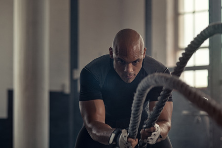 Man in sportswear doing battle ropes functional training at crossfit centre. Determined trainer making waves with ropes while exercising strength. Athlete working out with battle rope at industrial gym.