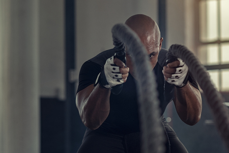 Strong athlete doing exercises with rope at crossfit gym. Bald african man working out with ropes at cross fit gym. Fitness strong man pulling rope at fitness center.