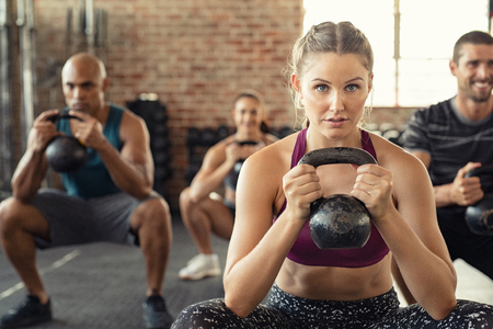 Group of fit people holding kettle bell during squatting exercise at crossfit gym. Fitness girl and men lifting kettlebell during strength training exercising. Group of young people doing squat with kettle bell.