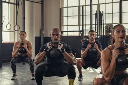 Fitness-Frauen und entschlossene Männer, die im Crossfit-Fitnessstudio mit Kettlebell trainieren. Gruppe junger Leute, die zusammen mit Hocken eine Kettlebell-Übung machen. Multiethnische Gruppe der Fitnessklasse, die beim Halten des Gewichts Hockenübungen macht. Standard-Bild