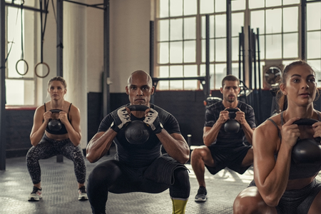 Fitness women and determined men exercising with kettlebell at crossfit gym. Group of young people doing a kettle bell exercise along with squatting. Multiethnic group of fit class doing crouch exercise while holding weight. Banco de Imagens