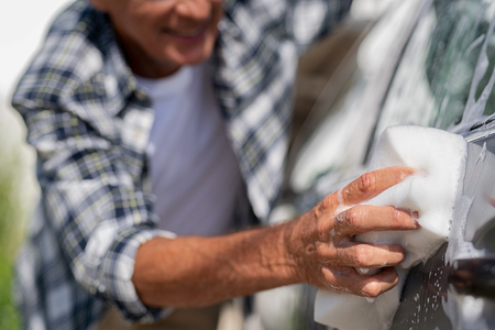 Man washing gray car with soapy sponge. Closeup of senior man hand holding soap sponge while washing car. Old wrinkled hand using white foam to clean his auto.