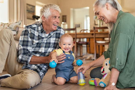 Smiling grandchild with grandparents playing with balls at home. Happy grandson with grandmother and grandfather playing with toys on floor at home. Senior woman and old man playing with little cute boy.