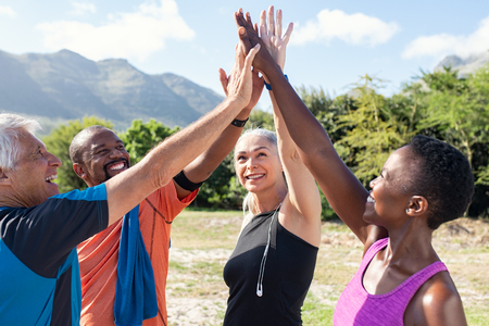Happy fitness multiethnic class giving high five after completing exercise session. Group of sweaty mature men and sporty women giving high five and looking up. Smiling friends celebrate their success.