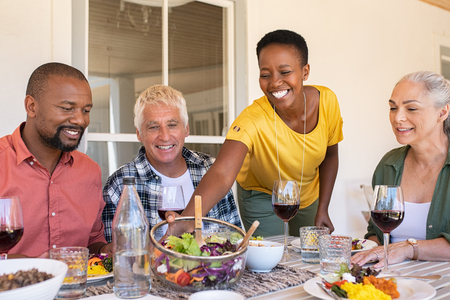 Cheerful black woman serving bowl of fresh salad to guests during lunch. Mature woman serving food while family members enjoying lunch with wine. Happy senior couple and african couple having lunch together in summer.