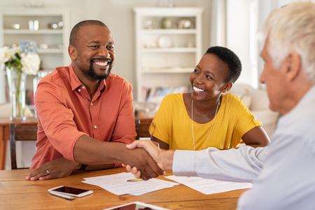 Reifer schwarzer Ehemann, der einem leitenden Agenten bei der Kreditaufnahme die Hand schüttelt. Glückliches afrikanisches Paar, das mit Handschlag einen Vertrag mit einem Finanzberater für Investitionen abschließt. Mann, der den Kaufvertrag mit einem Handschlag mit dem Immobilienmakler abschließt. Standard-Bild