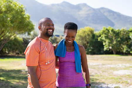 Cheerful black couple resting together after jogging in the park. Happy mature man and beautiful woman laughing while resting after running. Smiling woman and man taking a break after fitness training, copy space.