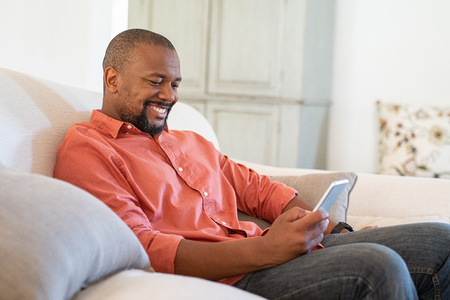 Happy black man using smart phone while relaxing at home. Smiling mature man at home sitting on couch reading phone message. African american guy download app for his cellphone.