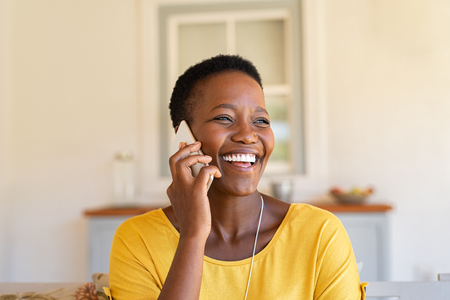 Smiling african american woman talking on the phone. Mature black woman in conversation using mobile phone while laughing. Young cheerful lady having fun during a funny conversation call. Banque d'images