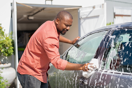 Middle aged black man cleaning his car outside the garage in the driveway. Mature african man cleaning automobile with sponge at car wash. Casual guy washing car with sponge and foam. Imagens