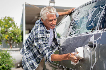 Happy senior man washing car with soap and foam. Old retired man cleaning automobile with sponge in a sunny day.  Satisfied driver washing his gray car near the garage. Imagens
