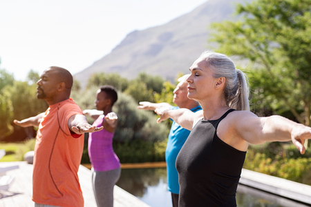 Group of senior people with closed eyes stretching arms outdoor. Happy mature people doing breathing exercise near pool. Yoga class with women and men doing breath exercise with outstretched arms. Balance and meditation concept.