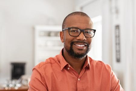 Homme mûr souriant portant des lunettes regardant la caméra. Portrait d'un homme noir confiant à la maison. Entrepreneur prospère se sentant satisfait.