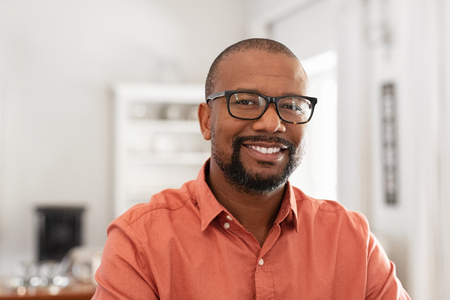 Lächelnder reifer Mann mit Brille an der Kamera. Porträt des schwarzen selbstbewussten Mannes zu Hause. Erfolgreicher Unternehmer, der zufrieden ist.