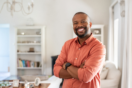 Portrait of smiling mature man with beard standing with crossed arms. Confident african man with folded arms at home looking at camera. Happy senior in casual feeling good. Imagens