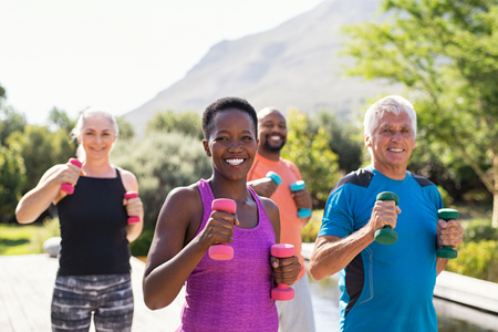Group of mature happy people using dumbbells for workout session. Multiethnic group of smiling women and senior men exercising with dumbbells outdoor. Cheerful people doing workout with weight lifting dumbbells and looking at camera.