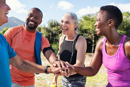 Rire des sportifs seniors et multiethniques se rassemblant au parc. Joyeux groupe d'hommes et de femmes souriant et empilant les mains en plein air. Équipe multiethnique en sueur acclamant après un entraînement intense.