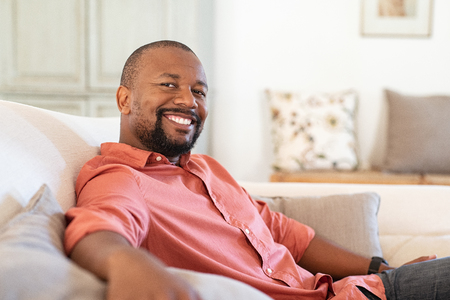 Portrait of happy mature african american man sitting on couch. Satisfied black man looking at camera while resting in living room. Handsome senior relaxing at home on the sofa.