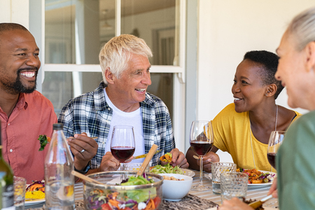 Happy mature friends having lunch together under the patio. Group of four smiling senior people enjoying meal with red wine together at home. Cheerful multiethnic women and men talking during dinner.