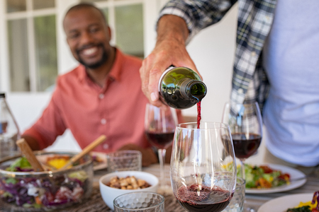 Closeup of senior man hand pouring red wine in glass. Host man serving alcohol during lunch with friends. Red wine poured into a glass with black mature man in background enjoying lunch.