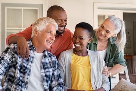 Amici allegri seduti in cortile godendosi il pomeriggio insieme. Un gruppo di quattro persone mature sedute fuori casa e ridenti. Uomo anziano felice e donna anziana che si divertono con una coppia africana matura.