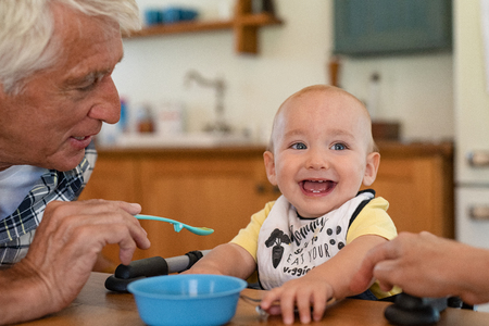 Happy grandfather feeding liquid food to grandson wearing bib. Cute adorable toddler eating food with senior man. Funny little boy looking away while man feeding with healhty fruit puree, baby food. Фото со стока