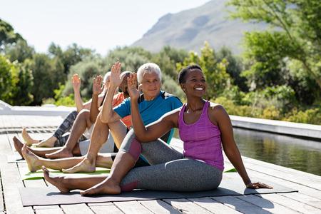 Uomini anziani e donne mature che fanno esercizio di yoga vicino alla piscina all'aperto. Persone multietniche in fila che praticano esercizi di stretching. Gruppo di sportivi di mezza età che praticano lezione di pilates. Archivio Fotografico
