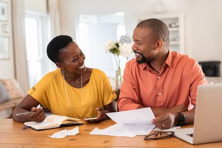 Alegre pareja sentada y gestionando los gastos en casa. Feliz hombre y mujer africanos pagando facturas juntos y gestionando el presupuesto. Pareja sonriente negra comprobando la contabilidad y las facturas mientras se miran.
