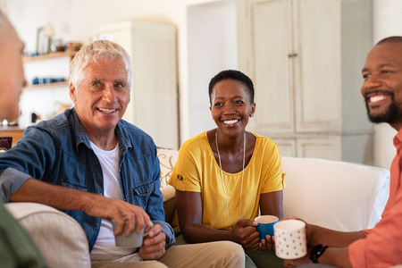 Group of multiethnic friends talking and drinking tea at home. Mature and senior couple chatting together while sitting on couch. Happy man and smiling woman looking at each other while in conversation at home and drinking coffee.