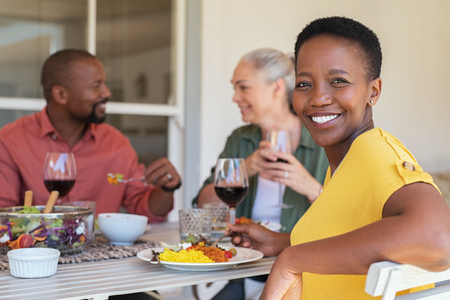Happy mature african woman looking at camera while having lunch with her friends in background. Portrait of laughing black woman enjoying brunch with senior people. Smiling casual lady and multiethnic couple eating and drinking together. Imagens