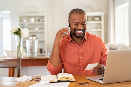 Smiling african man using laptop at home while checking home finance. Happy mature man looking at invoice while talking on phone with bank.  Man checking receipt and bill while talking at phone with insurance agent.